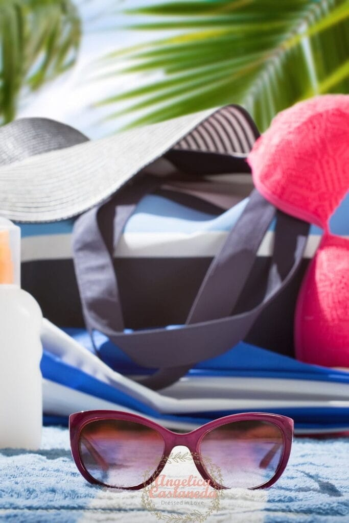 Pink sun glasses, white bottle, blue and white beach bag, navy blue and white sun hat and pink bathing suit top on a blue and white towel perfect for a beach vacation packing list.