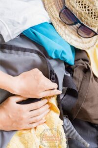 Woman's hands closing a travel laundry bag in her luggage.