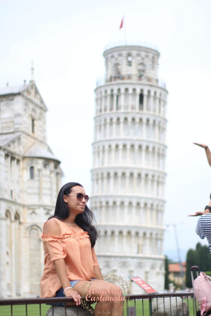 Woman sitting in front on The Leaning Tower of Pisa